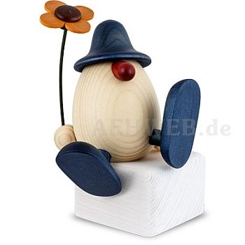 Eierkopf Alfons mit Blume auf Kante sitzend oder tanzend blau