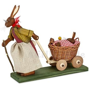 Osterhasengroßmutter mit Hasenbaby im Wagen mit roter Decke