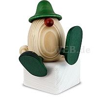 Eierkopf Alfons auf Kante sitzend oder tanzend grün