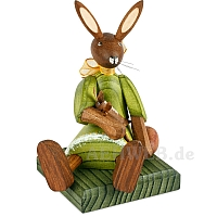 Easter bunny girl sitting with green dress and doll