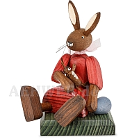 Easter bunny girl sitting with red dress and doll