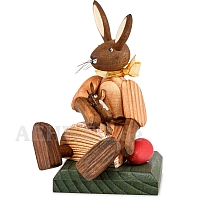 Easter bunny girl sitting with orange dress and doll