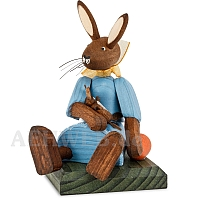 Easter bunny girl sitting with blue dress and doll